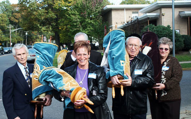 Carrying Torah scrolls in the procession are, from left, Allan Zucker, Lois Pollinger, Hal Kravetz, and Evelyn Zucker.