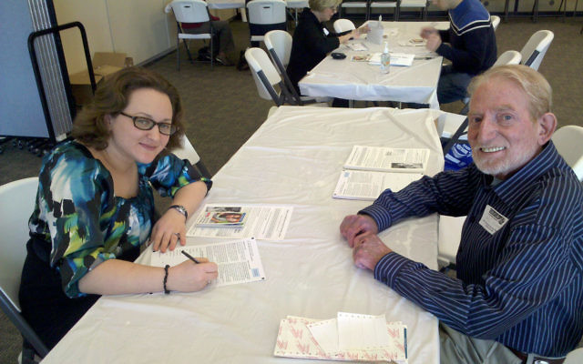 Mel Cohen, whose life was saved three years ago by a stem cell transplant, with Sasha Goldfarb, who is filling out a form during a Dec. 6 bone marrow drive at Temple Beth Miriam.