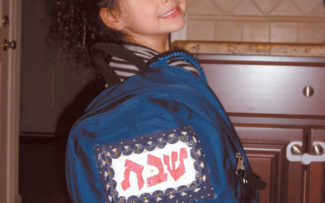 Alexa Tanzer, a member of the Solomon Schechter pre-kindergarten class, arrives home with the Shabbat Backpack.