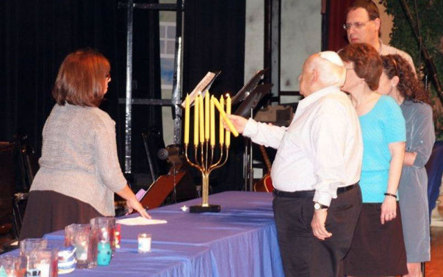 A survivor and members of his family light a memorial candle during the May 1 Yom Hashoa ceremony at the JCC in Deal.