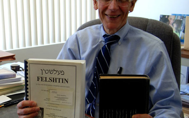 Sidney Shaievitz, in his Bloomfield law office, shows the Felshtin memorial volume and the work-in-progress English translation. Photo by Elaine Durbach