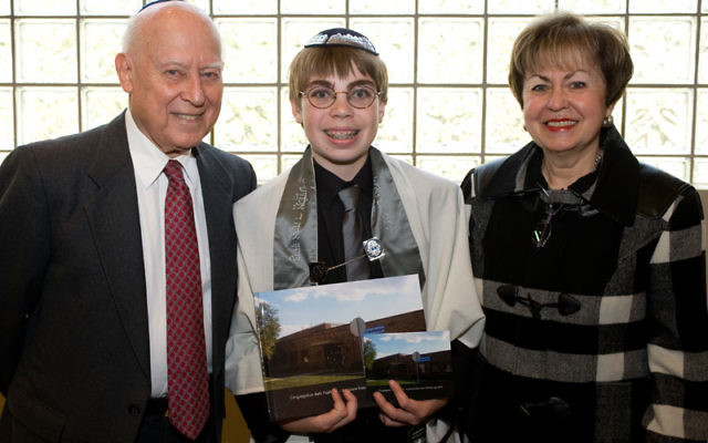 Ethan Solender at his Oct. 30, 2010, bar mitzva, flanked by former JHS president Bob Max and JHS executive director Linda Forgosh. Solender created a pictorial history of his Summit synagogue, right. Photo by Amy Hand
