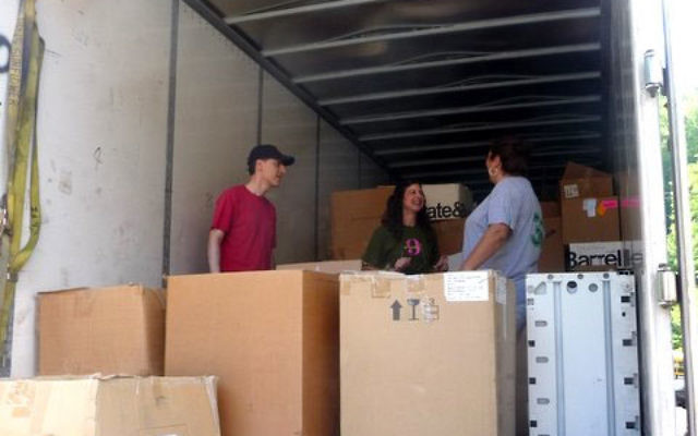 """Unloading the truck for the """"shop"""" in Kentucky are, from left, Steve Moehlman, Naomi Gruer, and a McRoberts resident. Photos courtesy Art Fredman"""