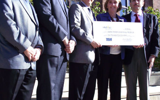 Displaying the check representing $2,500 given to the Greater Newark Conservancy by Oheb Shalom Congregation to help renovate the Prince Street building that was once its home are, from left, Oheb Shalom president, Michael Schechner, and religious leade
