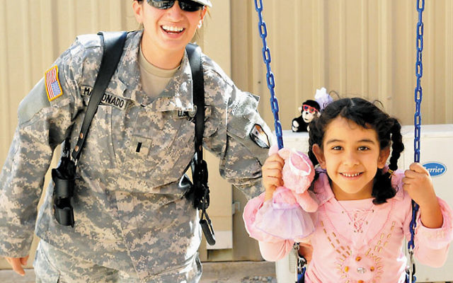 Corey Fefferman, shown during her military service in Iraq, had a practice of playing with Iraqi children who had come to visit detained parents. Photo courtesy Ava Reinfeld/Kevin Fefferman