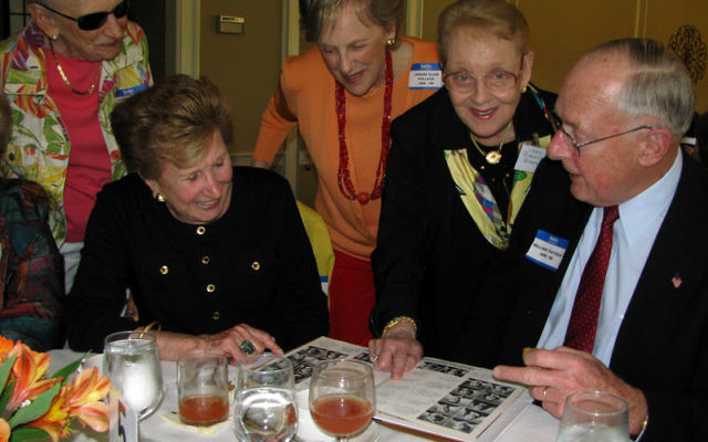 Classmates share a look at the Weequahic High School class of 1948 yearbook. Photos by Robert Wiener