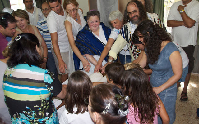 As the Torah scroll was dedicated, Ronni Pressman, in tallit and kipa, chanted a passage with a yad she brought as a gift for Kibbutz Beit Oren. Photos by Randy Pressman