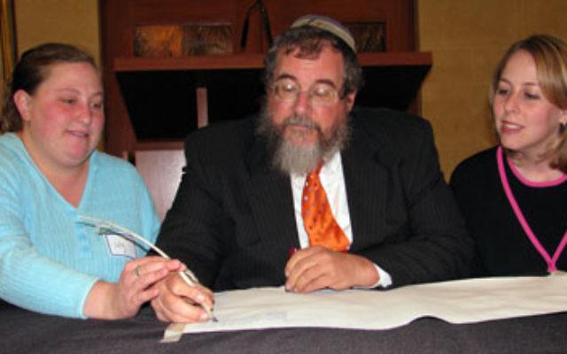 Lily Moritz, left, helps Rabbi Zerach Greenfield inscribe a letter in a Torah as Sharey Tefilo-Israel's Rabbi Ellie Lynn Miller looks on.