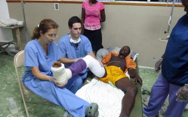 Barbara Minkowitz teaches Ari Faiwiszewski how to set a cast for a Haitian man with a broken leg. Photos courtesy Barbara Minkowitz