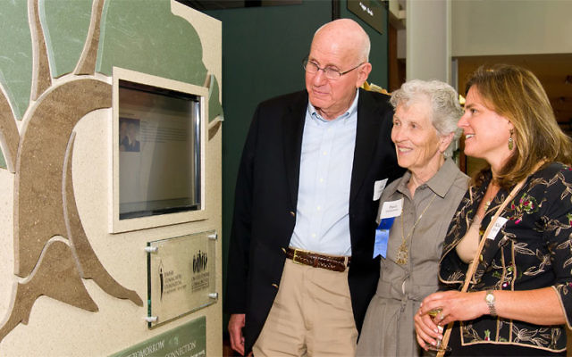 Jerry and Paula Gottesman are joined by Kim Hirsh, right, development officer at Jewish Community Foundation of MetroWest, as they view the new MetroWest Tomorrow display at the Aidekman campus in Whippany.