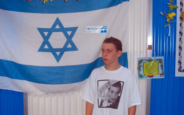 Gilad Falkenstein, 13, of West Orange in his family's sukka. Gilad is selling T-shirts, like the one he is wearing, to help support efforts on behalf of Gilad Shalit, the Israeli soldier captured by Hamas in 2006.