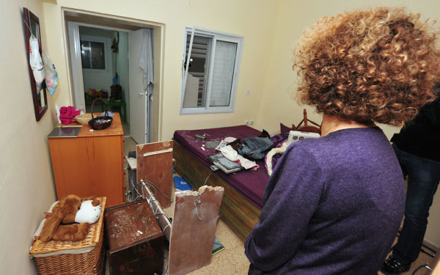 Reut Geltzer surveys the damage to her home on Kibbutz Kfar Aza following a rocket attack from Gaza. The family was not at home when the rocket struck. Photo by Rafael Ben-Ari/Chameleons Eye