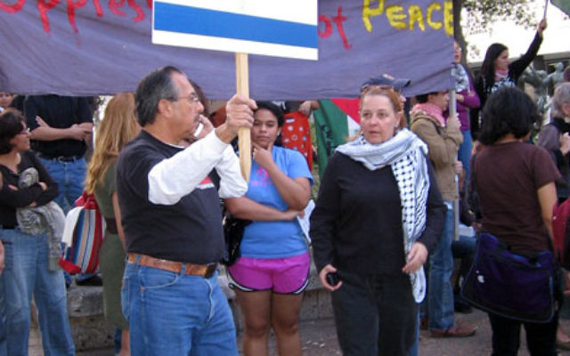 A counter-demonstrator at a 2009 pro-Israel rally at the University of Texas in Austin holds a swastika superimposed on an Israeli flag. Photo courtesy Anti-Defamation League