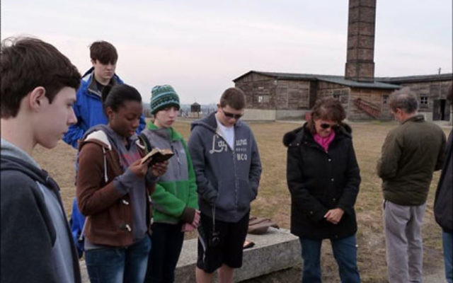 Students from Newark Academy, during their March trip to Holocaust sites in Poland and Prague, read memorial passages outside the crematorium at the Majdanek concentration camp.