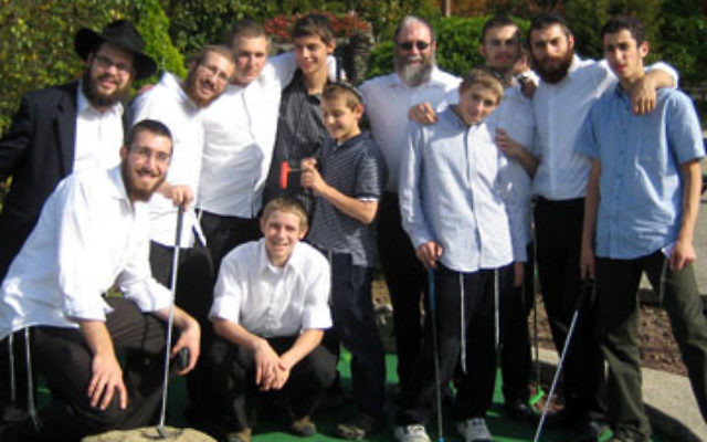 At Mt. Freedom Golf's miniature golf course are Ukrainian-Jewish orphans and their counselors, along with head counselor Mendel Eichenblatt, bottom row, left, and Sukkos 09 organizer Moshe Morgenstern, top row, fifth from left.