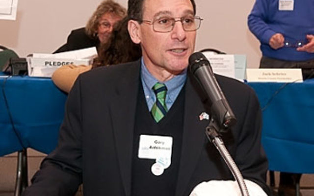 "Gary Aidekman addresses the gathering at last December's Super Sunday; as he leaves the presidency of United Jewish Communities of MetroWest NJ, he says, ""It's been a challenging time, but I'm proud of our response."""
