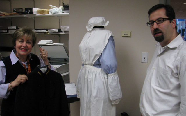 Linda Forgosh, executive director of the Jewish Historical Society of MetroWest, and Joshua Feinberg, project curator at the Yeshiva University Museum, inspect replicas of vintage uniforms worn by nurses at Newark Beth Israel Medical Center. Photo by Robe