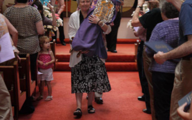 Karen Solomon, who was in the synagogue's first confirmation class and who was married in the sanctuary's first wedding ceremony, led the procession of Torah scrolls out of the sanctuary, which will undergo renovation this summer. Photo by Joh