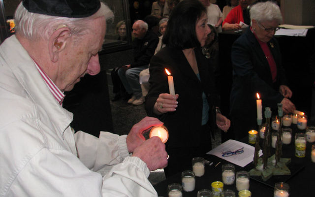 Survivor Fred Heyman of Morristown lights a candle in memory of those who died in the Holocaust. Photo by Robert Wiener