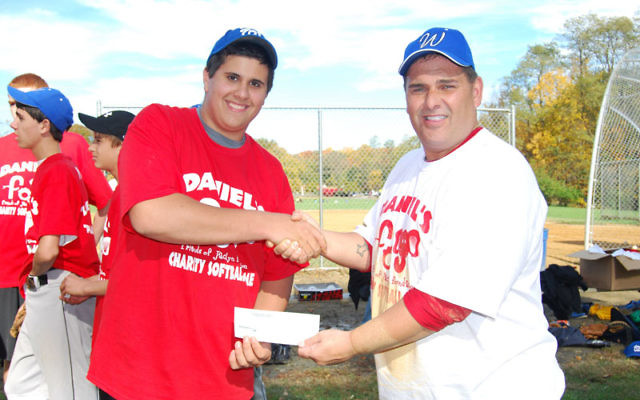 Dan Berke, left, receives a check from Gary Moore, on behalf of the Westfield Police Benevolent Association, to support his charity baseball game last year.