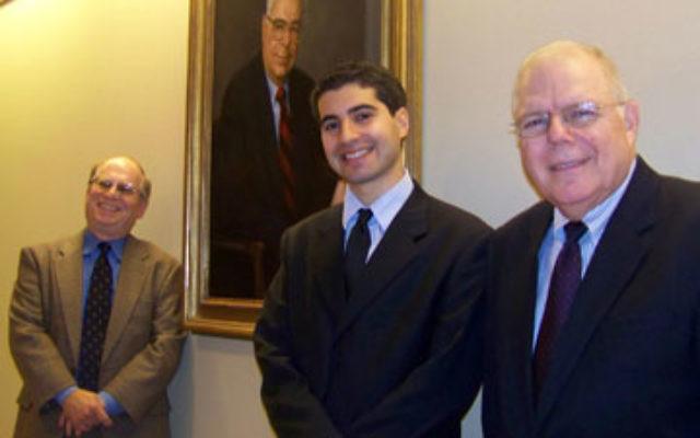 Standing before a portrait of Alan Lowenstein are new Lowenstein fellow Nir Buchler, center, Max L. Kleinman, left, and Bruce Shoulson.