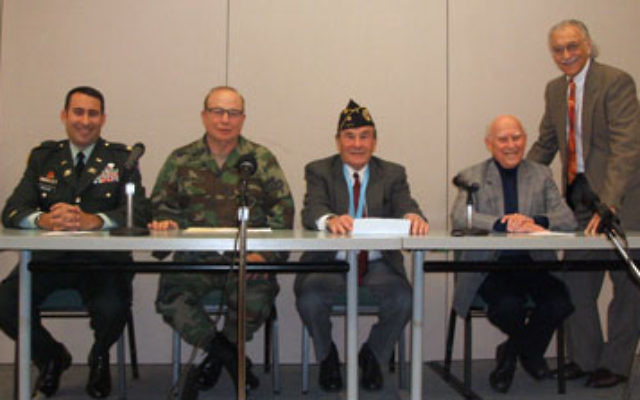Telling their war stories are, from left, veterans Marc Krauss, Arthur Weintraub, Myron Katz, and Bob Max, while Jewish Historical Society president Howard Kiesel looks on.