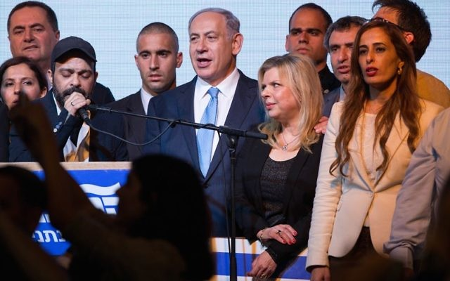 Israeli Prime Minister Benjamin Netanyahu and his wife, Sara, sing the Israeli anthem along with members of his Likud party, at the party headquarters in Tel Aviv, March 18, 2015, after the exit polls in the Israeli general elections were announced, with