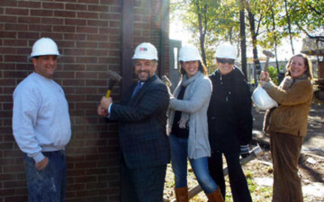 At the symbolic start of the demolition of a fraternity house Nov. 6 to prepare for construction of the new Rutgers Hillel are, from left, contractor Dan Matarese and Hillel leaders executive director Andrew Getraer, president Hilary Nehar of South Orange