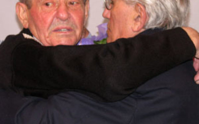 Bronislaw Firuta, left, hugs Joseph Bonder, the man he sheltered during the Holocaust, moments after their emotional reunion at John F. Kennedy Airport.