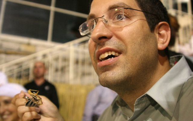 NJJN correspondent Gil Hoffman prepares to eat a locust (yes, they're kosher), but held off until a helpful waiter removed its crunchy outsides.