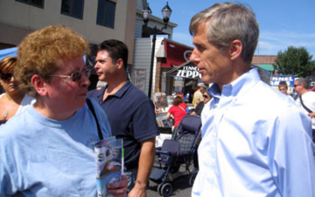 Independent candidate Chris Daggett speaks with a voter at a Labor Day celebration in Linden.