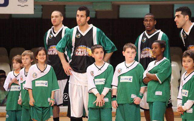 Members of the Maccabi Haifa basketball team share the court with kids from the Maccabi Haifa Youth program. Photo courtesy Maccabi Haifa