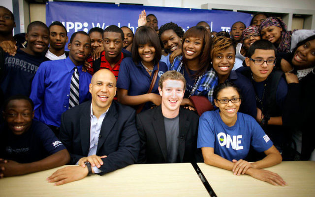 """Facebook founder Mark Zuckerberg, center, joins students and Newark Mayor Cory Booker in a Sept. 25 visit to the KIPP Newark Collegiate Academy in Newark. KIPP, an acronym for the """"Knowledge Is Power Program,"""" has 99 free college-preparatory"""