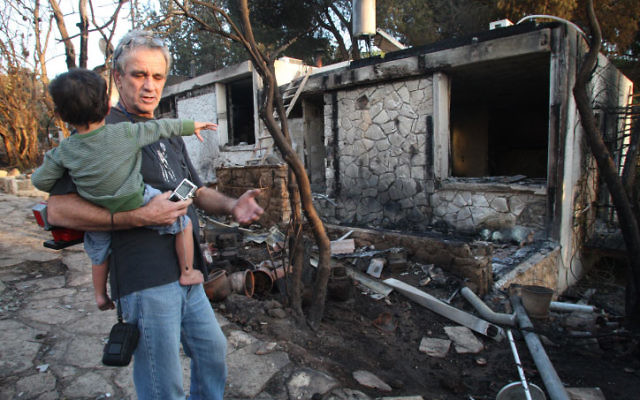 A father and son look at their house in Ein Hod, near Haifa, that was burned down in the fire that ravaged the Carmel Forest, Dec. 5.