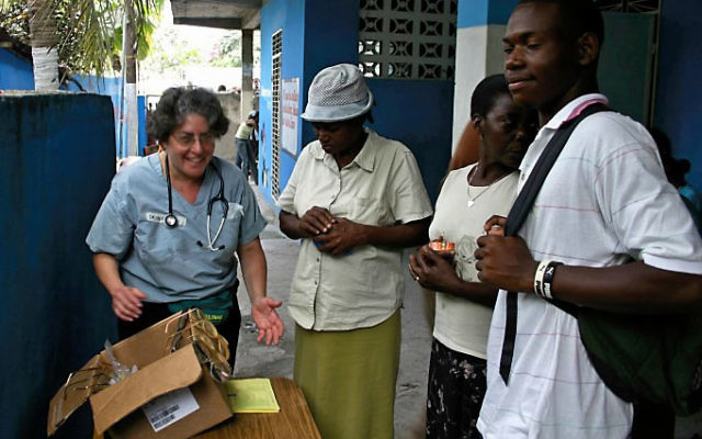 Dr. Benetta Miller, a surgeon from South Orange, helps Haitians find the right pair of donated eyeglasses.