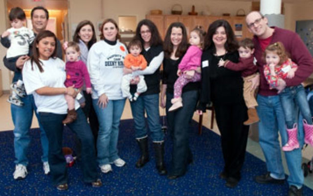 Participating in the Dec. 6 Super Sunday fund-raiser for United Jewish Communities of MetroWest NJ on the Aidekman campus are, from left, Brody Early Childhood Center parent David Solomon and his son, teacher Cinthia Garnique with a Brody center baby, par