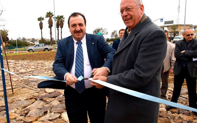 Arad Mayor Gideon Bar-Lev, right, assisted by National Highway Authority director-general Alex Vishnitzer, cuts the ribbon on the new project to widen the highway that leads into the Negev town.