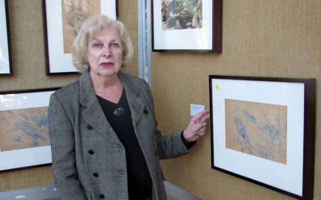 Maxine Giannini examines her late husband's sketches of the Normandy invasion, June 1945.