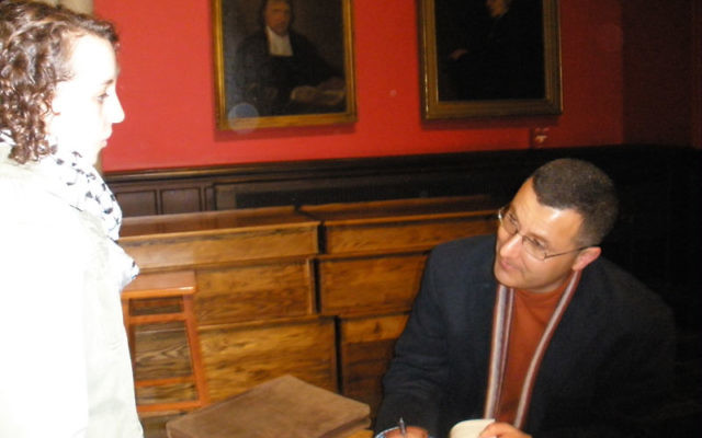 Omar Barghouti, a leader of the campaign to boycott Israel, signs a copy of his book during an April 12 appearance at Rutgers University in New Brunswick. Photo by Debra Rubin