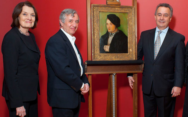Simon Goodman, right, grandson of the original owners of Hans Baldung Grien's Portrait of a Young Man, receives the 1509 painting in a Jan. 14 ceremony at the Zimmerli Art Museum from museum director Suzanne Delehanty and Dr. Philip Furmans