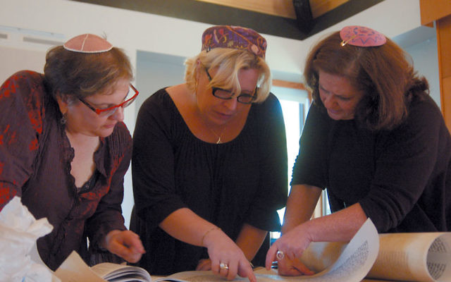Torah scribes, from left, Linda Coppleson, Rabbi Chana Klebansky, and Rachel Reichhardt, discuss the placement of text on a panel before it is sewn onto the rest of the scroll, Oct. 13 in Seattle. Photo by Joel Magalnick/JTNews