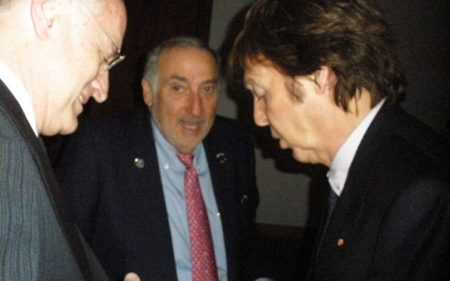 Ex-Beatle Sir Paul McCartney, right, signs an autograph for Malcolm Hoenlein, left, executive vice chair of the Conference of Presidents of Major American Jewish Organizations, who was keynote speaker at the Chabad dinner; looking on is dinner honoree Mik