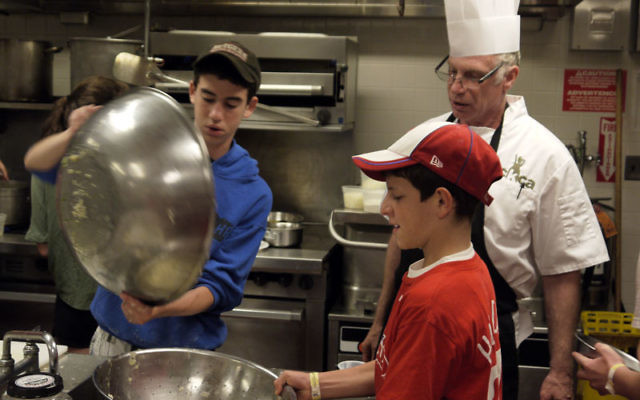 Justin Fiszer, left, and Yona Kornsgold learn how to make potato latkes under the supervision of Chef Avram Wiseman in a culinary arts specialty camp program launched by Camp Ramah in the Berkshires this summer. Photos by Johanna Ginsberg