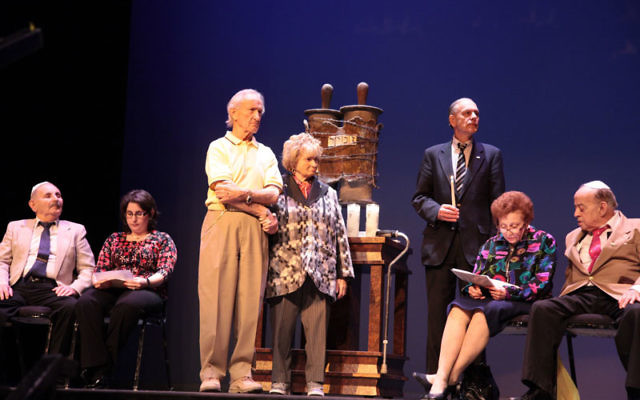 Edward Mosberg, standing, accompanied by his wife, Cecille, was among the survivors who lit candles in memory of the Six Million at the annual Yom Hashoa event at Kean University; with them are, from left, Abraham Klein and his daughter Susann Krane, Dr.