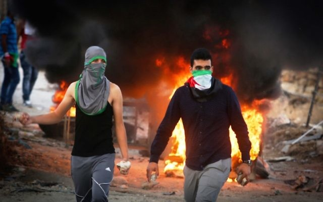 Palestinian protesters in the West Bank throwing stones and burning tires during clashes with Israeli security forces over the Al-Aqsa mosque compound, Sept. 30, 2015. (Flash90)
