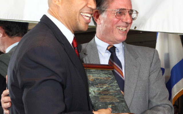 Newark Mayor Cory Booker, left, receives his Shomer Tzedek-Guardian of Justice Award from Lionel Kaplan, vice president for Israel and overseas for the Jewish Federation of Princeton Mercer Bucks.