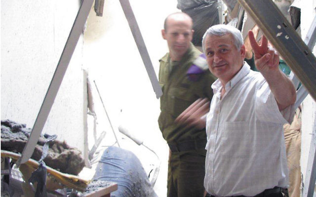 Alon Schuster, the mayor of Israel's Sha'ar Hanegev region, inspects rocket damage to a hydrotherapy center near Sapir College. Photo courtesy UJC MetroWest