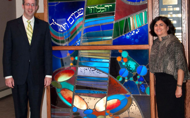 East Brunswick Jewish Center's Rabbi Aaron Benson and congregation copresident Amy Rothman Schonfeld with a stained-glass window that was part of the original JFK Airport International Synagogue.