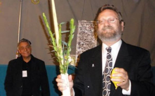 Rabbi Robert Wolkoff demonstrates how the lulav and etrog are used during an interfaith Sukkot celebration with Christians and Muslims Oct. 6 at Congregation B'nai Tikvah in North Brunswick.
