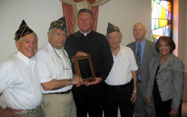 Presenting a plaque of appreciation to Father Edward Flanagan, center, at the Nativity of Our Lord in Monroe, are, from left, JWV Post 609 member Bernie Passer, post commander Frank Slavin, post member Shelly Bloom, and church members Steve Marone and A